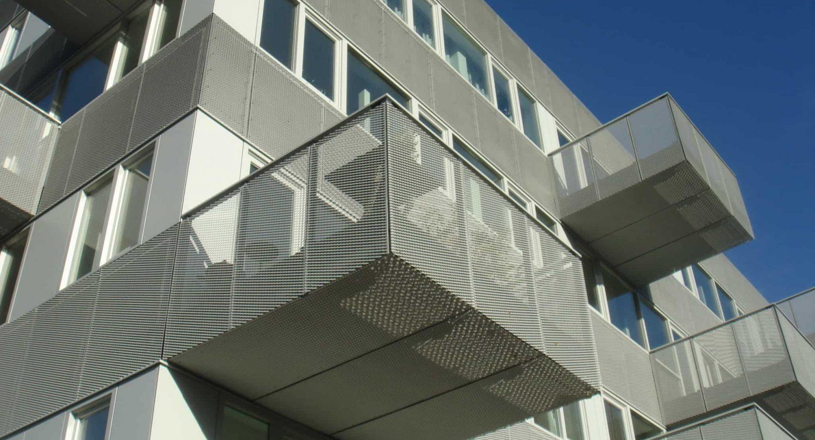 Onderaanzicht van het appartementencomplex Boogie Woogie waar de gevels en balkons voorzien zijn van strekmetaal