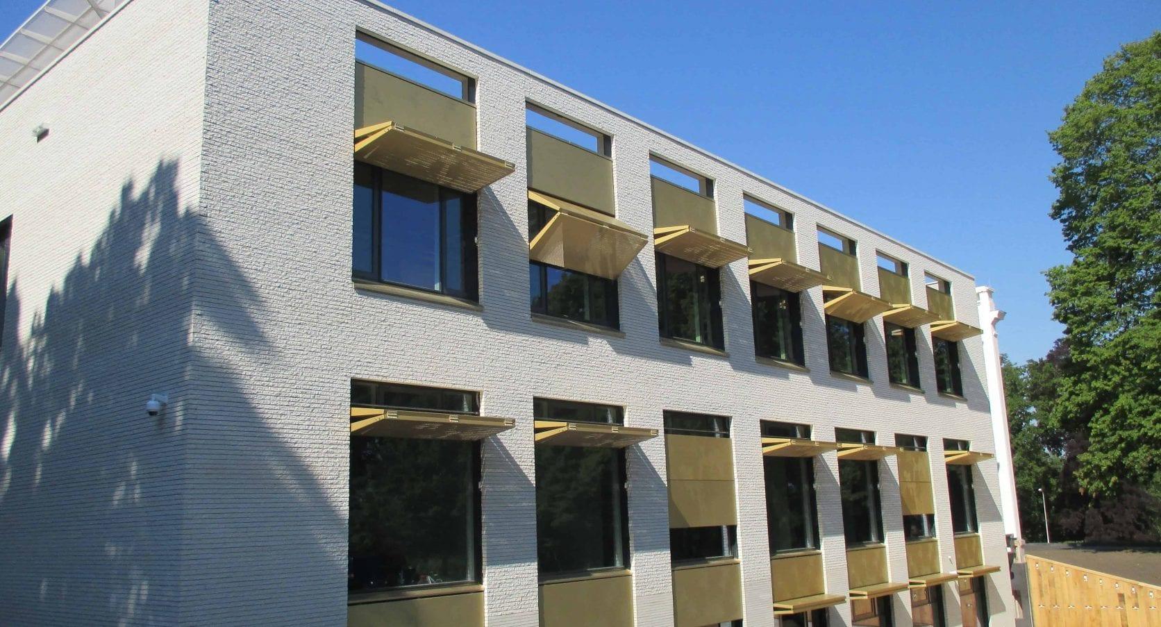 Zijkant van het Gemeentehuis in Bloemendaal met uitzicht op de automatische en zonwerende luiken in goudkleur