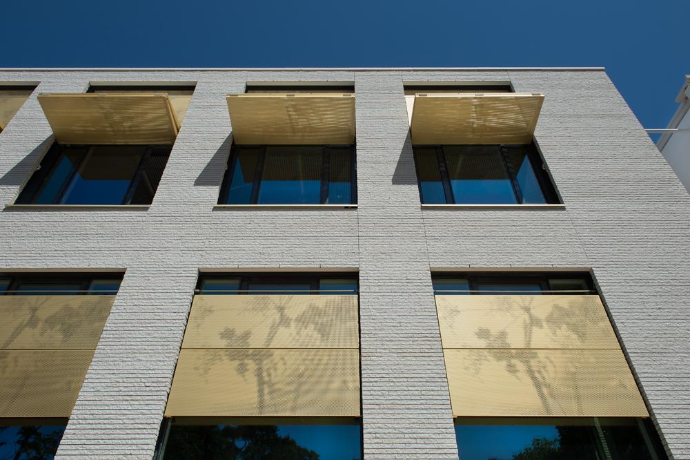 Automatische en zonwerende luiken in goud kleur van het Gemeentehuis in Bloemendaal