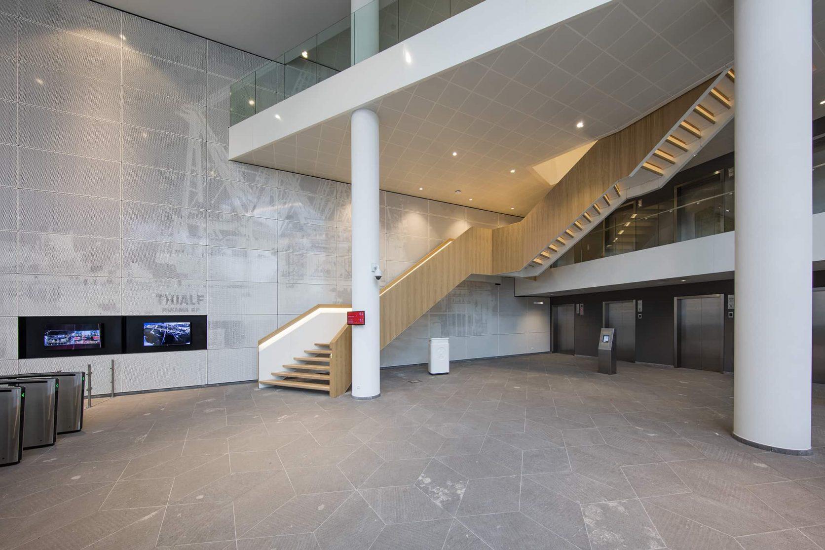 In de centrale hal van Heerema in Leiden is een wand met geperforeerd staal met fotoprint toegepast