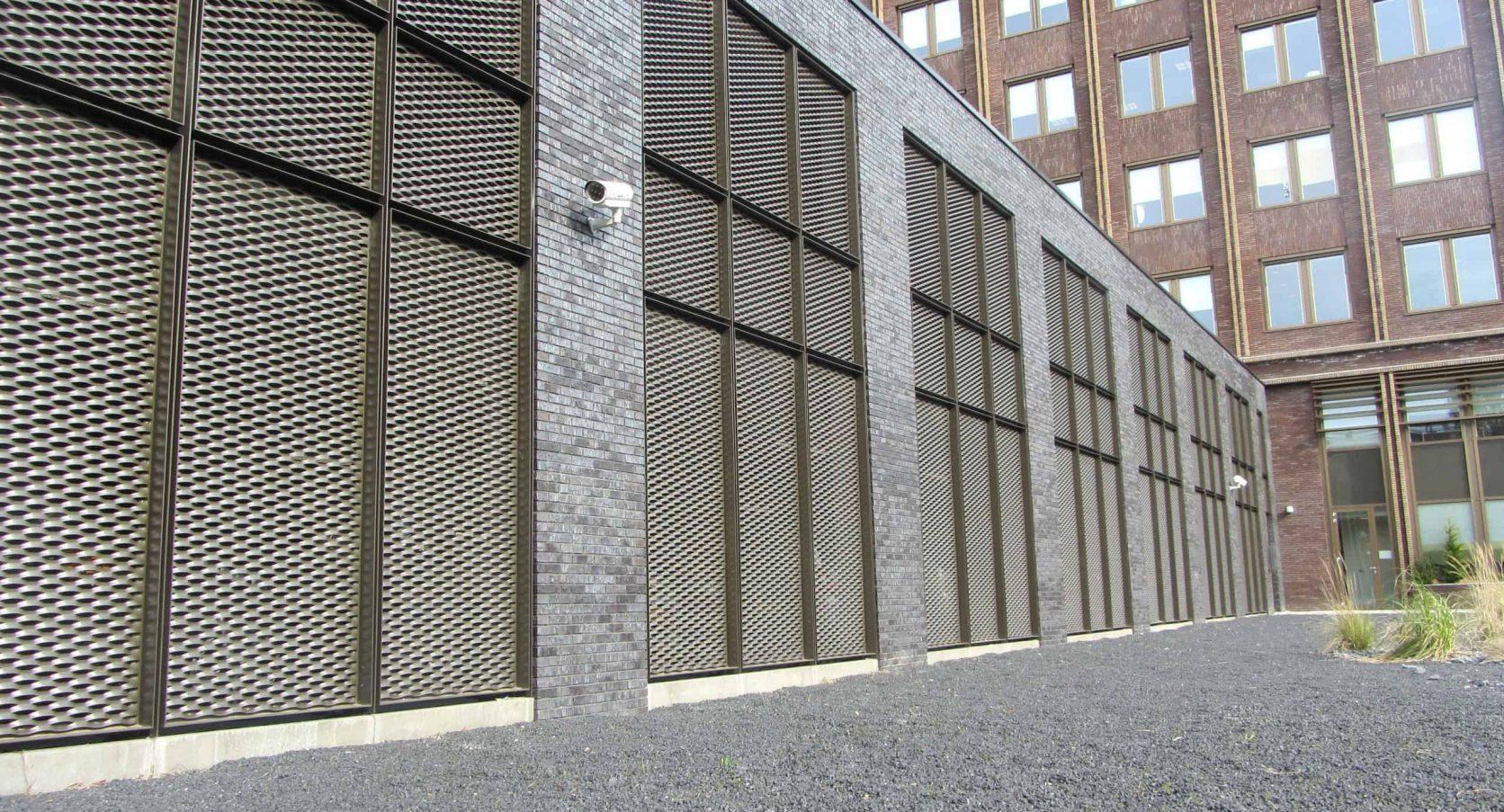 Zijaanzicht van de Parkeergarage Technolution in Gouda met gevelbekleding van MD Strekmetaal in de kleur donkerblond