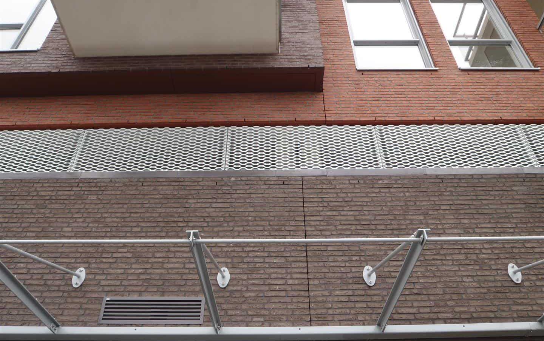Detail van de MD Strekmetaal plint Appartementencomplex Portage in Zaltbommel, zorgt voor ventilatie en daglicht rondom het garagedek