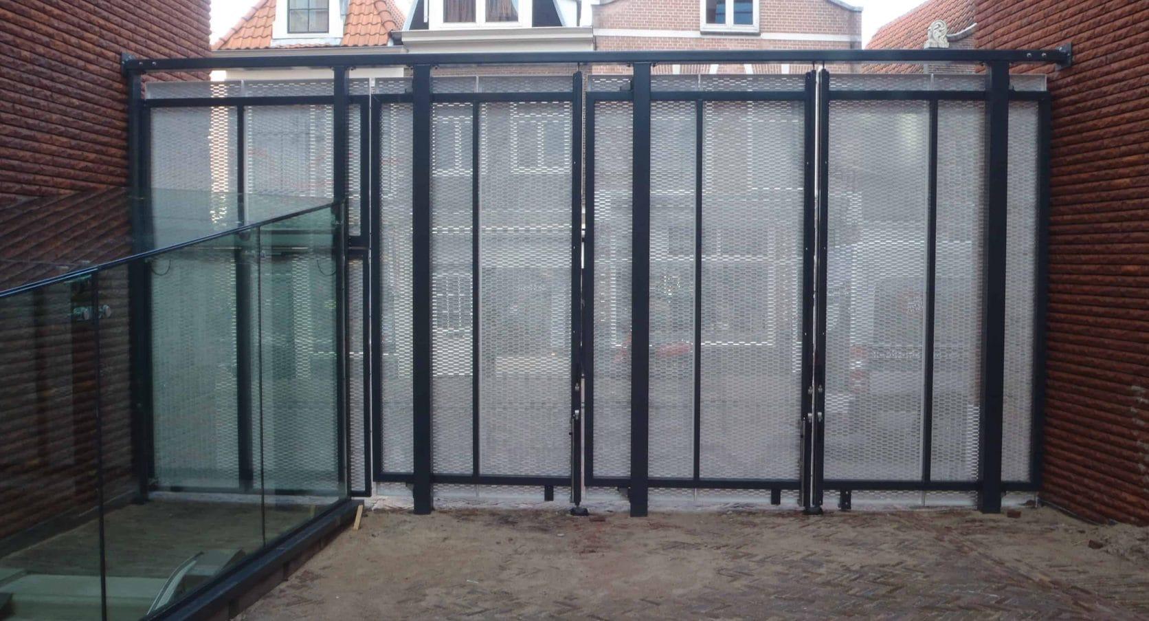 Close-up vanaf de binnenkant van de toegangsdeuren van MD Strekmetaal van het Stadskantoor Zijlpoort in Haarlem
