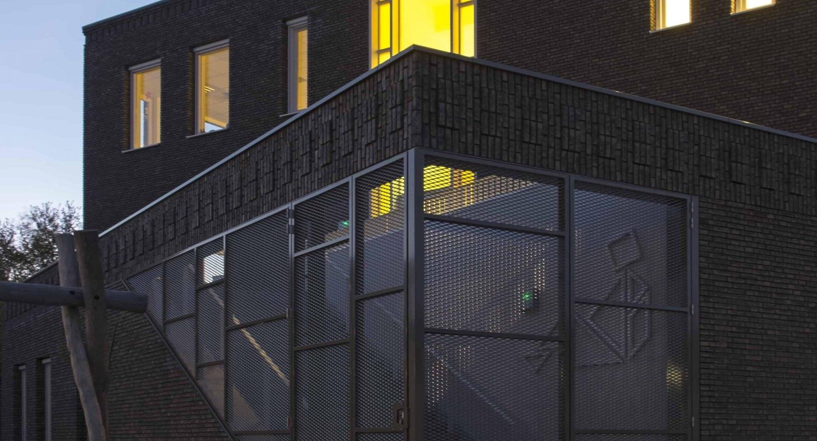 Vooraanzicht van de strekmetalen poort van de PWA school in Tiel