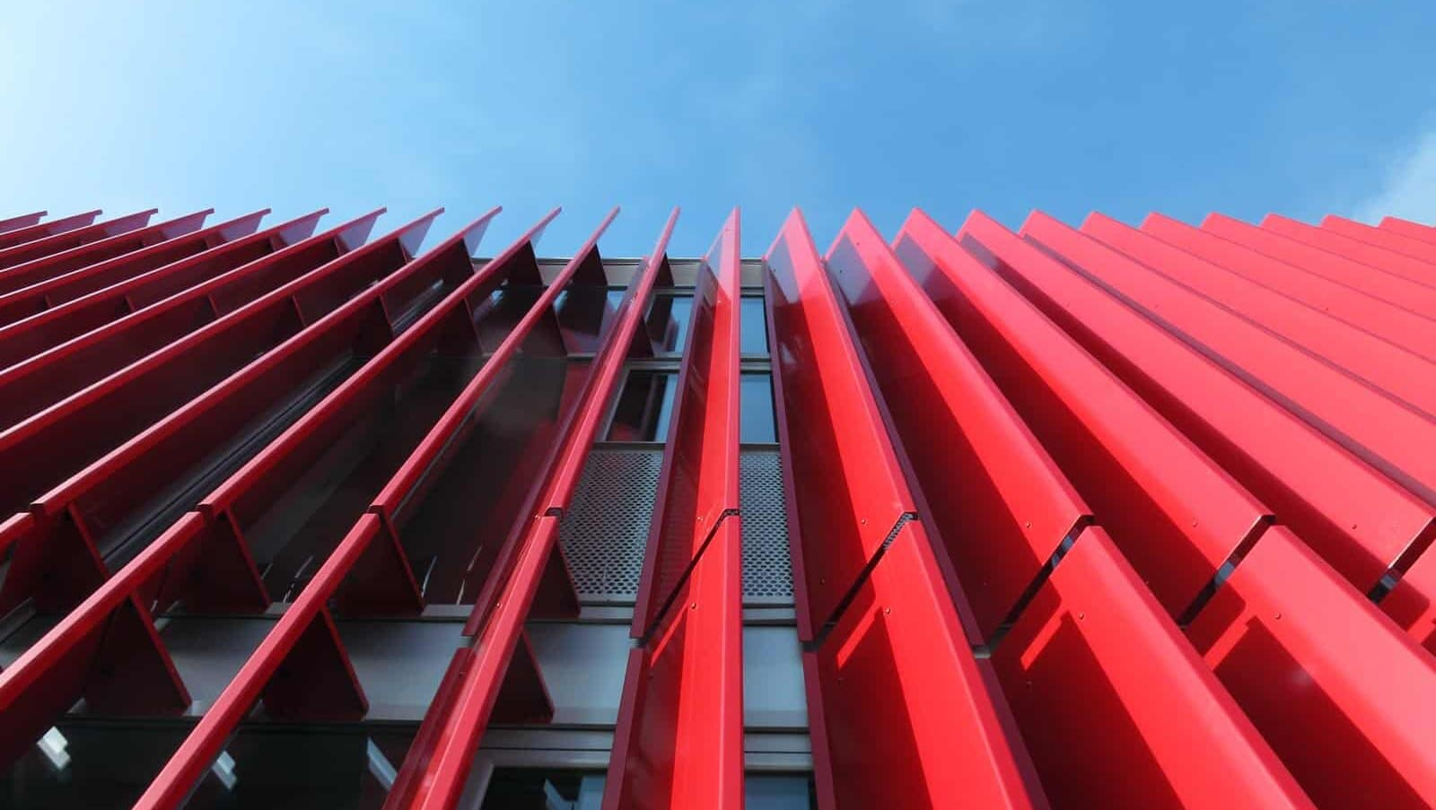 Close-up van de rode gecoate aluminium lamellen als gevelbekleding voor het Kantoor Macchine per Caffee Espresso in Timisoara te Roemenië